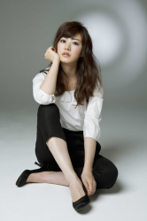 Ms. Rikomi is a Japanese & Asian mature beauty fashion model, she is wearing a white shirt and black pants, she sitting on the floor grasping her knees on the floor, her height is 171 cm and she is tall, her style is very good.