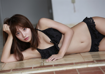 The beautiful & cute Japanese & Asian model, freelance announcer, TV personality wearing a black bikini swimsuit, her name is Ms. Ayaka, she is lying on the floor.