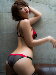 Ms. Asami is a Japanese & Asian sexy beauty gravure idol (bikini model) & actress, her bust is 89 cm, her breasts are relatively large, and her body is very graceful, she is wearing fishnet tights, black gloves, black & red lingerie, collar, she stands beside a brown sofa, she is a sexually attractive woman.