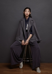 Ms. Anju was born in 1995 & she is 176 cm tall, she is a Japanese & Asian fashion model & catwalk model (runway model), this is a full-length photo of her tall girl, she is a tall & slender, she is dressed in dark gray and sits in a chair.